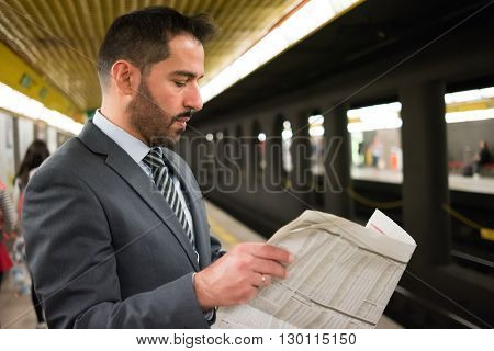 Commuter reading a newspaper while waiting for the subway train