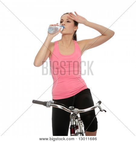 Attractive brunette woman with bike drinking water. over white background