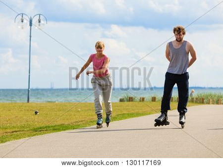 Love romance leisure outdoor fitness sport concept. Teenagers together on skates. Young girl and boy spend time riding rollerskates in park.