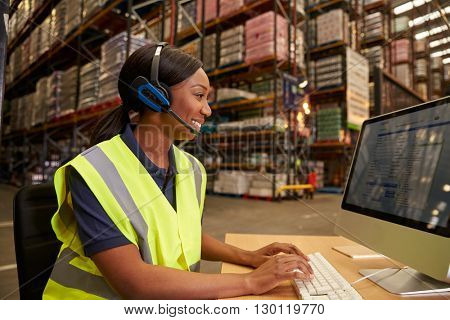 Woman with headset working in on-site office of a warehouse