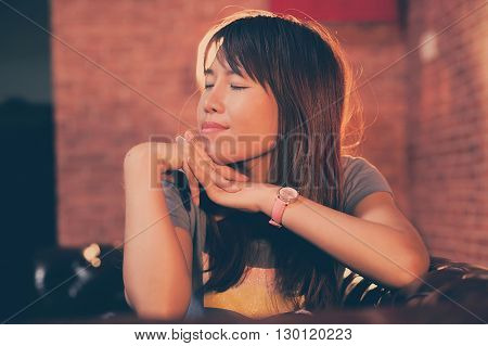 asian women sit on sofa and closing eyes