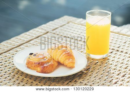 continental breakfast croissant in plate and orange juice on the table soft focus.