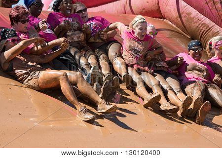 HAMPTON, GA - APRIL 2016: A group of muddy women holds hands as they slide down toward a mud pit at the Dirty Girl Mud Run obstacle course event in Hampton GA on April 23 2016 .