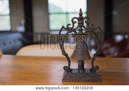 Beautiful antique metal bell with nice design on table in room with sofa set in day time/Beautiful antique metal bell