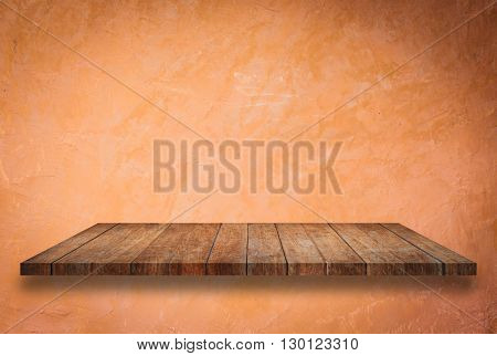 Empty perspective top wooden shelf on orange wall background