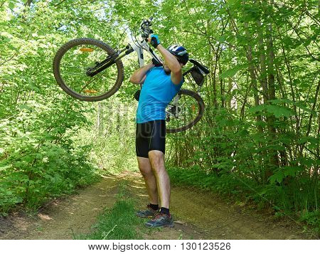 Cyclist Man Carries Bicycle In Green Forest In Summer.