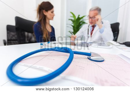 Doctor talking to a patient. Focus on the stethoscope in the foreground.