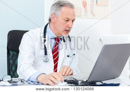 Senior doctor working at his laptop