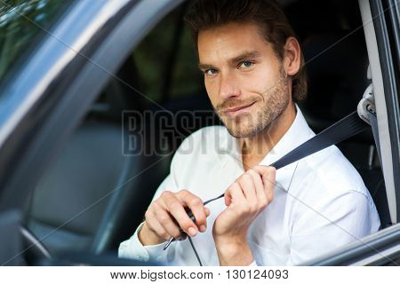 Young man fastening seat belt on his car