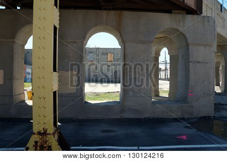 An abandoned building, as seen between the support columns of a railroad bridge, in downtown Joliet.