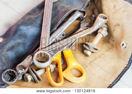 Set of tools in old leather bag on the cement floor