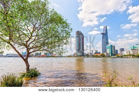 Ho Chi Minh City, Vietnam - January 19th, 2016: Skyscrapers riverside sunny day, in front of riparian cork toward busy urban expressed economic development in opening up Ho Chi Minh city, Vietnam