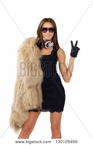 DJ woman with earphones in fur coat and sunglasses poses on isolated studio background. High fashion look