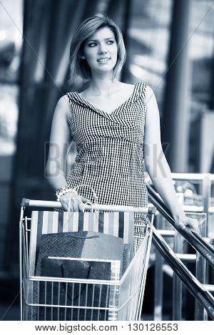 Beautiful blond with shopping cart near supermarket