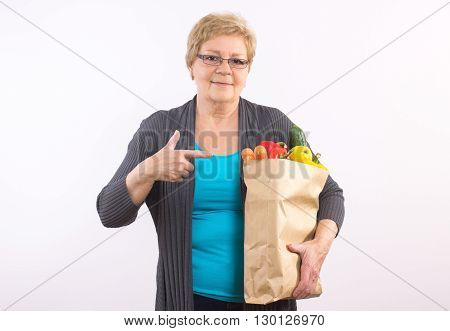 Happy smiling elderly senior woman showing shopping bag with fruits and vegetables healthy nutrition in old age