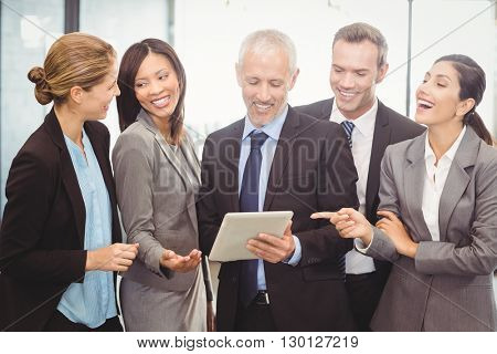Happy businesspeople interacting and using and digital tablet in office