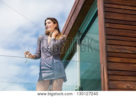 Low angle view of gorgeuos woman standing by glass railing at balcony
