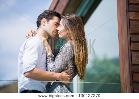 Low angle view of romantic young couple kissing in balcony at resort