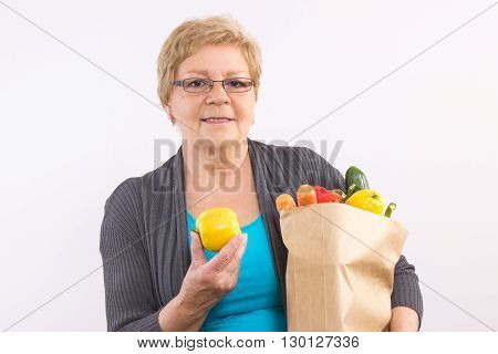 Happy smiling elderly senior woman holding fruits and vegetables in shopping bag healthy nutrition in old age