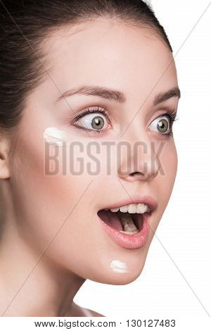Beautiful face of young woman with cosmetic cream on a cheek. Skin care concept. Closeup portrait isolated on white.