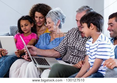 Happy family using laptop and digital tablet in living room at home