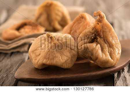 dried figs on a dark wooden spoon