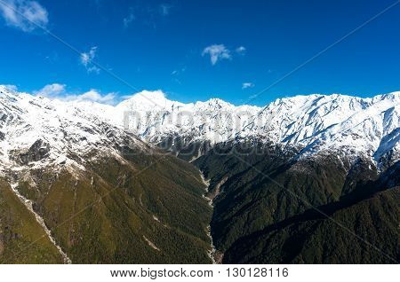 Aerial view of New Zealand mountains. View from above on snow caped mountains with green forest over slopes and Whataroa river. New Zealand wilderness landscape