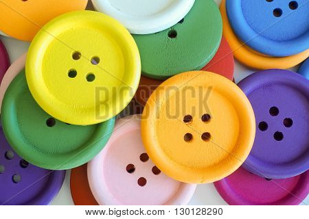 A collection of boldly colored painted wooden buttons.