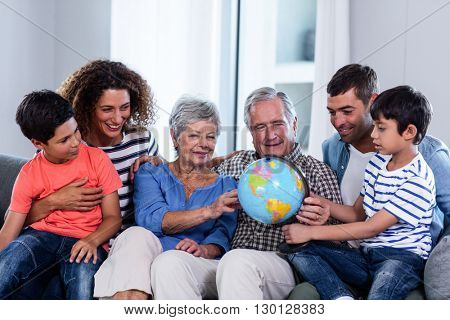 Happy family looking at a globe in living room at home