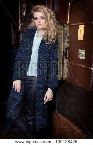 Beautiful young sexy woman with long blond hair, bright make-up Smokey Eyes wearing a sweater next to a dresser and a bar with a catalog of clothing collection autumn fashion spring style