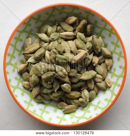 Dried Cardamom pods in a small colorful ceramic bowl.