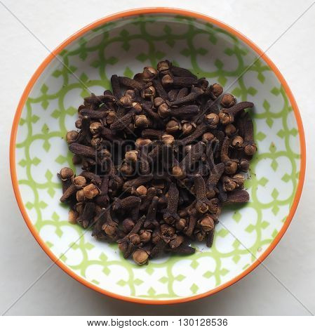 Whole Dried Cloves in a small colorful ceramic bowl.