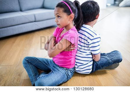 Upset siblings ignoring each other at home