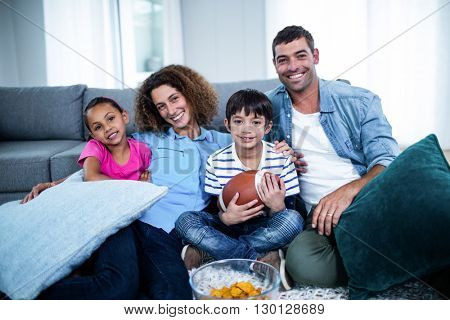 Portrait of family watching american football match on television at home