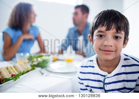 Portrait of boy smiling and parents having breakfast in background