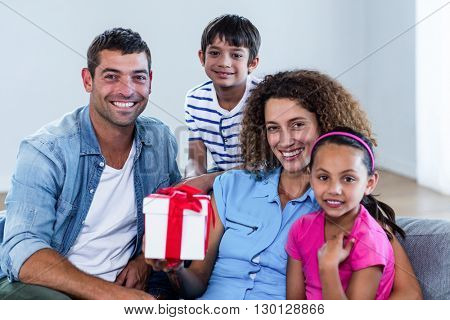 Portrait of family sitting on sofa with a gift in living room