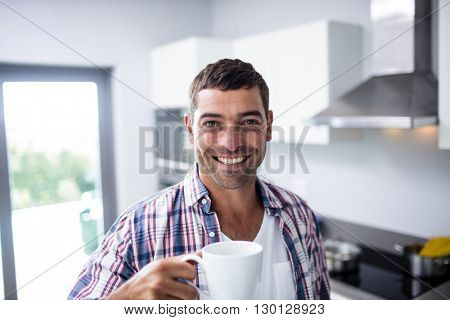 Portrait of happy man having coffee in kitchen