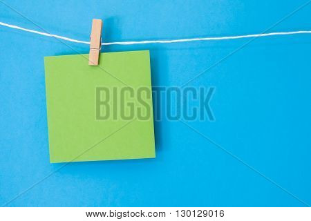 A bright green blank note square hanging on a white string line in front of a bright blue colored background.
