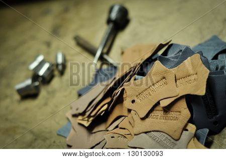 Made In India Leather Embossing with embossing tools. Leather lables, embossed with genuine leather and Made in India are in sharp focus, but embossing tools are in the background. No human face or body part is not visible in the image.