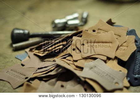 Genuine leather and made in India embossed on leather labels. All leather labels, embossed clearly and in sharp focus. The embossing tools are in the background. No human body part included in the photograph.