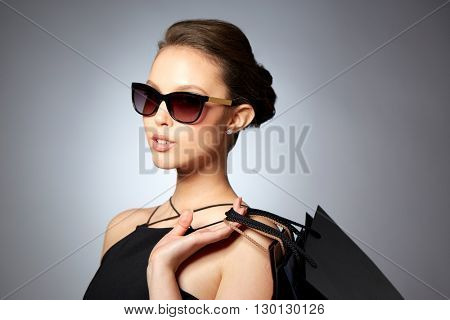 sale, fashion, people and luxury concept - happy beautiful young woman in black sunglasses with shopping bags over gray background