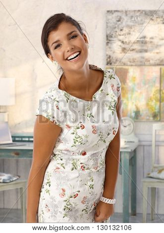 Attractive caucasian young brunette smiling lady at vintage home. Standing, wearing colorful dress, looking at camera, toothy smile.