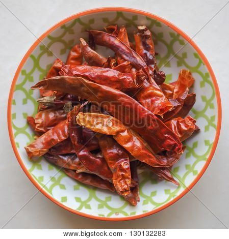 Dried red chillies in a small colorful ceramic bowl.