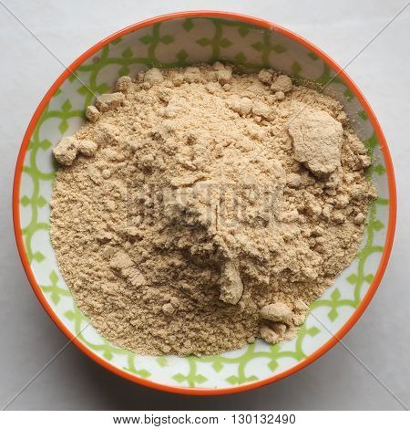 Ground Ginger / Ginger powder in a small colorful ceramic bowl.