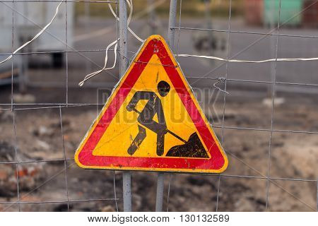 The road sign with a silhouette of the digging person hangs on a grid before a hole