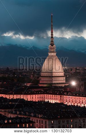 Cityscape of Torino (Turin Italy) at dusk with details of the Mole Antonelliana towering on the city and glowing in the night. Wind storm over the Alps in the background. Toned image.