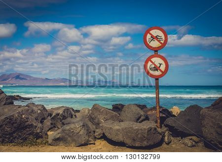 No swimming, no fishing signs on the coast in Corralejo, Fuerteventura, Canary Islands, Spain