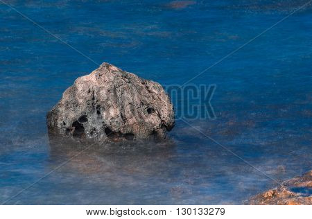 Large rock surrounded by silky blurred water on the coastline of Corralejo, Fuerteventura, Canary Island, Spain