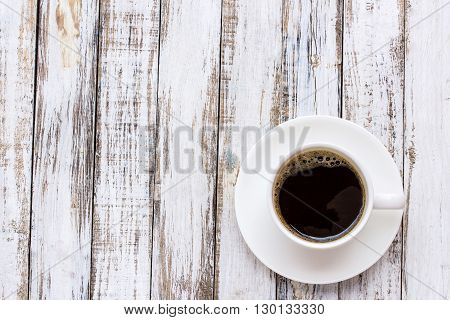 Coffee cup on white wooden table background. top view
