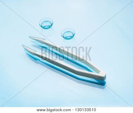 Contact lenses and tweezers on blue background